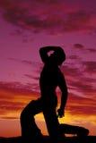 Vaquero de la silueta que ninguna genuflexión de la camisa una mano de la rodilla en el sombrero mira para arriba Fotografía de archivo