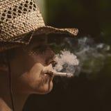 Vaquero en sombrero con la silueta del cigarro Imágenes de archivo libres de regalías