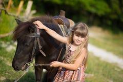 Vaquero hermoso de la muchacha del fermer lindo en vaqueros que disfruta de día de verano en vida del pueblo con las flores que l Imágenes de archivo libres de regalías