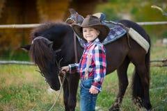 Vaquero hermoso del muchacho del fermer lindo en vaqueros que disfruta de día de verano en vida del pueblo con las flores que lle Fotos de archivo libres de regalías