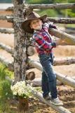 Vaquero hermoso del muchacho del fermer lindo en vaqueros que disfruta de día de verano en vida del pueblo con las flores que lle Imagenes de archivo