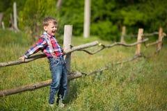 Vaquero hermoso del muchacho del fermer lindo en vaqueros que disfruta de día de verano en vida del pueblo con las flores que lle Fotografía de archivo libre de regalías