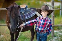 Vaquero hermoso del muchacho del fermer lindo en vaqueros que disfruta de día de verano en vida del pueblo con las flores que lle Foto de archivo libre de regalías