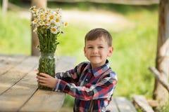 Vaquero hermoso del muchacho del fermer lindo en vaqueros que disfruta de día de verano en vida del pueblo con las flores que lle Fotografía de archivo