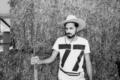 Vaquero joven barbudo hermoso que sostiene una bifurcación de la echada imágenes de archivo libres de regalías