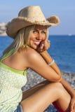 Vaquero que lleva Hat de la muchacha rubia de la mujer en la playa Imagen de archivo
