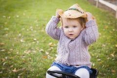 Vaquero que lleva Hat y el jugar del niño juguetón en Toy Tractor Outside Fotos de archivo libres de regalías