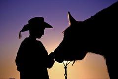 Vaquero y su silueta del caballo imagenes de archivo