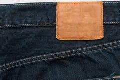 Vaqueros azules del dril de algodón con la etiqueta como fondo Imágenes de archivo libres de regalías