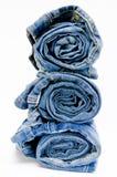 Vaqueros azules del dril de algodón del rollo dispuestos en pila Fotografía de archivo