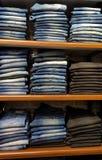 Vaqueros azules del dril de algodón en estante en una tienda de ropa imágenes de archivo libres de regalías