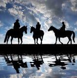 Vaqueros de la silueta con los caballos Fotos de archivo libres de regalías