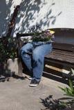 vaqueros del atajo adornados con las flores que se sientan en un banco a del jardín Fotografía de archivo libre de regalías