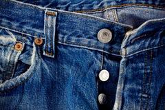 Vaqueros del botón de los vaqueros del fondo del denimand defectuoso y de la plata con una costura de la textura del dril de algo fotos de archivo