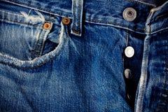 Vaqueros del botón de los vaqueros del fondo del denimand defectuoso y de la plata con una costura de la textura del dril de algo foto de archivo