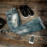 Vaqueros, gafas de sol, bolso y calzado rasgados de moda en una madera Fotos de archivo libres de regalías