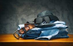 Vaqueros y camisa con los accesorios en la tabla de madera Fotografía de archivo