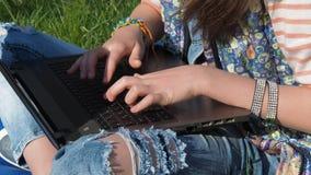 Vaqueros y un ordenador portátil Las manos de un adolescente en pulseras imprimen en un ordenador portátil Pantalones vaqueros de almacen de metraje de vídeo