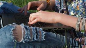 Vaqueros y un ordenador portátil Las manos de un adolescente en pulseras imprimen en un ordenador portátil Pantalones vaqueros de metrajes