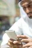 Varón árabe usando el teléfono elegante Foto de archivo