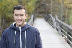 Varón étnico sonriente que camina a través de un puente Fotografía de archivo libre de regalías