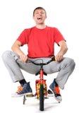 Varón absurdo en una bicicleta de los niños foto de archivo libre de regalías