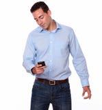 Varón adulto de moda usando su teléfono móvil Imagen de archivo