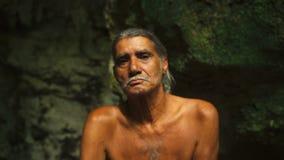 Varón adulto en los pantalones cortos que se sientan en una roca en una cueva almacen de video