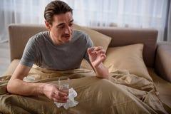 Varón adulto enfermo que toma la medicina en casa Imagen de archivo libre de regalías