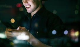 Varón adulto joven feliz usando un smartphone en un paisaje urbano de la noche Fotos de archivo
