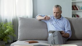 Varón adulto que se sienta en el sofá y que lee las noticias en la tableta, tecnologías modernas imagen de archivo