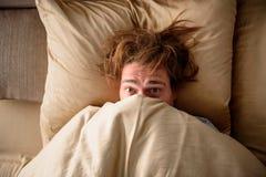 Varón adulto soñoliento que despierta para el trabajo en dormitorio imagen de archivo