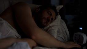 Varón adulto soñoliento que intenta apagar el despertador, falta de sueño, tensión imágenes de archivo libres de regalías