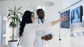 Varón africano joven y doctores de sexo femenino caucásicos que hablan de impresiones de la radiografía del paciente almacen de metraje de vídeo