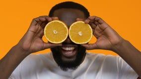 Varón africano juguetón que sostiene los ojos delanteros de las rebanadas anaranjadas, nutrición de la vitamina, salud metrajes