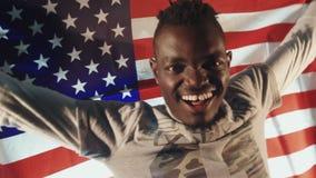 Varón afroamericano con la bandera americana en manos metrajes