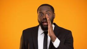 Varón afroamericano divertido en el formalwear que hace el aviso secreto, descuentos almacen de metraje de vídeo