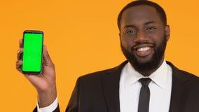Varón afroamericano en smartphone de la demostración del traje con la pantalla verde y el guiño almacen de metraje de vídeo