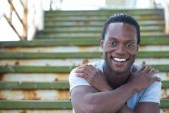 Varón afroamericano feliz que sonríe con los brazos cruzados Imagenes de archivo