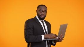 Varón afroamericano ocupado en el traje que trabaja en el ordenador portátil, crecimiento de la carrera, negocio almacen de metraje de vídeo
