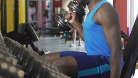 Varón afroamericano que hace la elevación-para arriba alterna de la pesa de gimnasia, bíceps creciente, entrenamiento metrajes