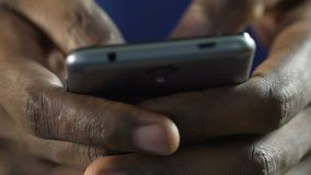 Varón afroamericano que mecanografía el mensaje rápido en el teléfono móvil, permaneciendo en contacto almacen de metraje de vídeo