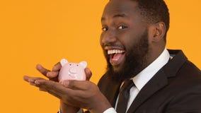 Varón afroamericano sonriente que sacude la hucha, presentes del depósito, actividades bancarias almacen de video