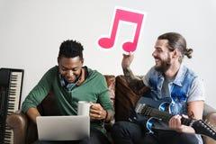 Varón afroamericano y caucásico en una nota musical de la tenencia de proceso del songwriting Fotografía de archivo libre de regalías
