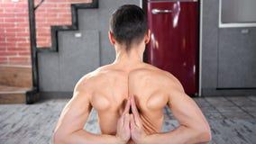 Varón apto muscular que hace gesto de manos del namaste detrás de la parte posterior que muestra estirando el primer medio almacen de metraje de vídeo