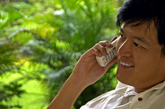 Varón asiático que charla feliz en el teléfono Imagenes de archivo