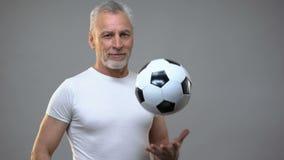 Varón atlético envejecido que juega con el balón de fútbol, entrenador de fútbol, forma de vida activa almacen de metraje de vídeo