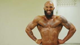 Varón atlético que muestra actitud delantera de la extensión del lat en el gimnasio, entrenando antes de competencia almacen de video