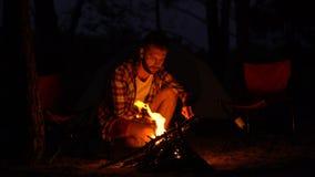 Varón barbudo que hace el fuego para el grupo de los amigos, soplando en las llamas, fin de semana activo almacen de video