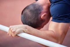 Varón cansado después de ejercitar en un área de entrenamiento, en la calle foto de archivo